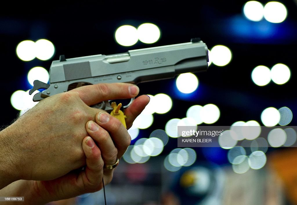 A convention goer handles a Ruger 1911 model semiautomatic pistol during the142nd annual National Rifle Association convention at the George R Brown...