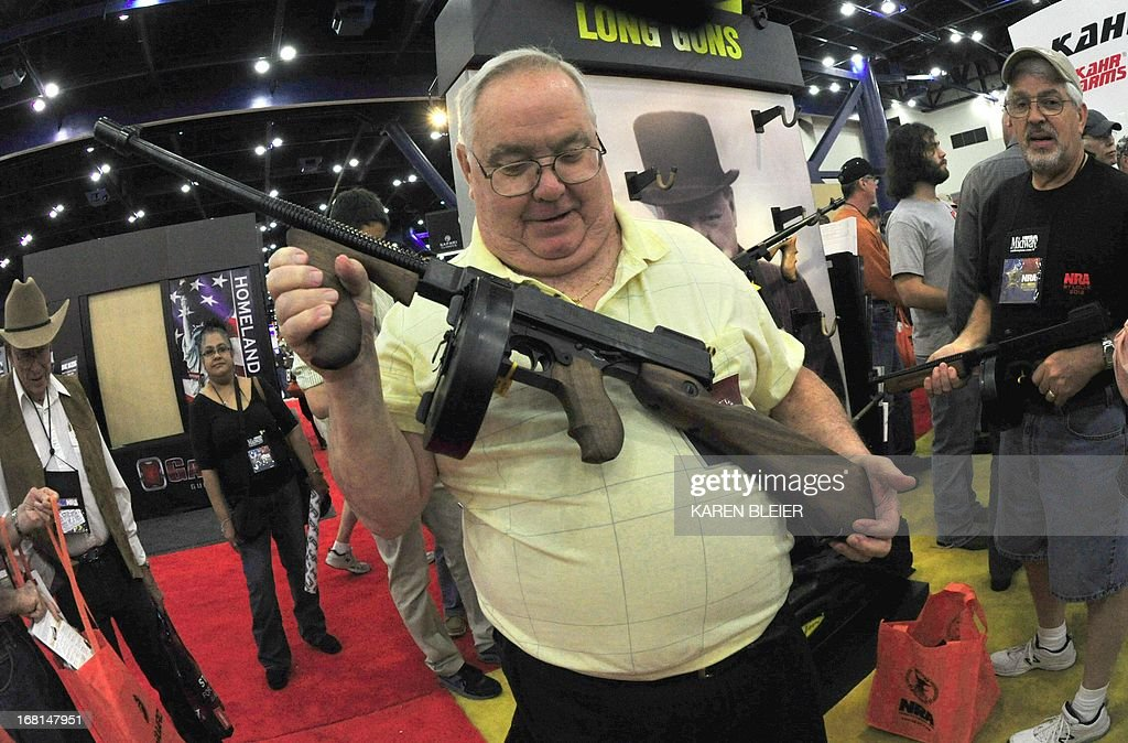 A convention goer holds a Thompson .45 submachine gun at the 142nd annual National Rifle Association(NRA) Convention at the George R. Brown Convention Center May 4, 2013 in Houston, Texas. The Thompson is an American submachine gun, invented by John T. Thompson in 1919, that became infamous during the Prohibition era. It was a common sight in the media of the time, being used by both law enforcement officers and criminals. The Thompson was also known informally as: the 'Tommy Gun', 'Trench Broom', 'Trench Sweeper', 'Chicago Typewriter', 'Chicago Piano', 'Chicago Style', 'Chicago Organ Grinder', and 'The Chopper'. AFP PHOTO / Karen BLEIER
