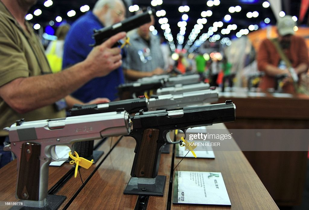 Convention goers look at various models of Ruger 1911 model semiautomatic pistols during the 142nd annual National Rifle Association convention at...
