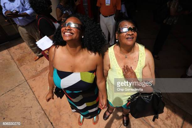 Convention goers step outside of the Marriott Resort and Spa at Grande Dunes to catch a glimpse of the solar eclipse August 21 2017 in Myrtle Beach...
