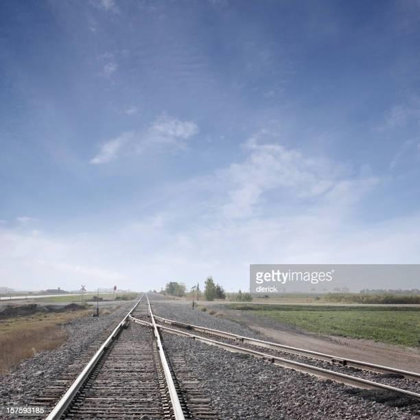 converging train tracks under big sky