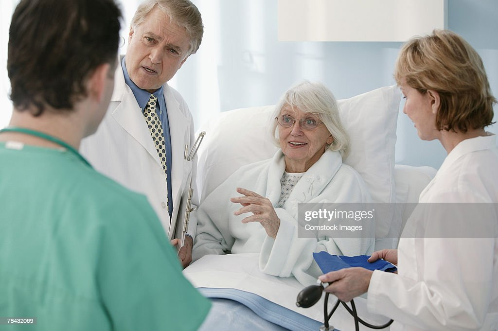 Conversation between doctors , nurse and patient : Stock Photo