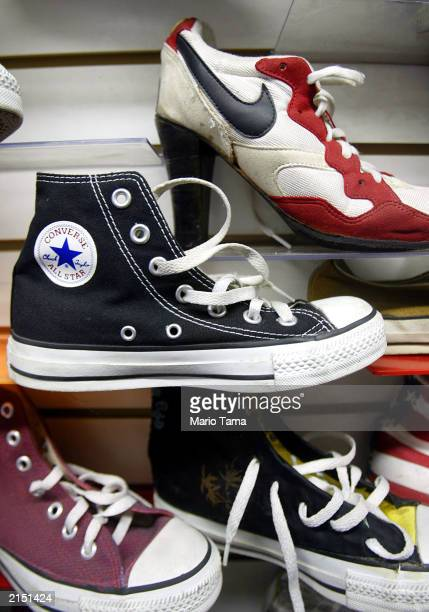 Converse 'Chuck Taylor' sneakers and a custom Nike high heel shoe sit on shelves July 10 2003 in New York City Nike announced it will buy rival...