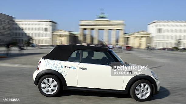 A convertible car of German carsharing company DriveNow manufactured by brand Mini is pictured in front of the Brandenburg Gate in Berlin on April 10...
