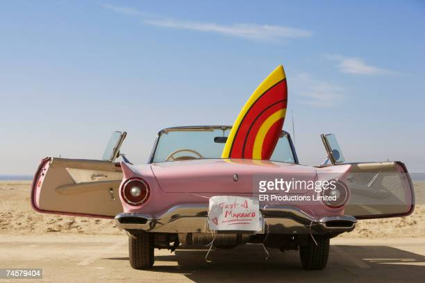 Convertible car with Just Married sign and surfboard