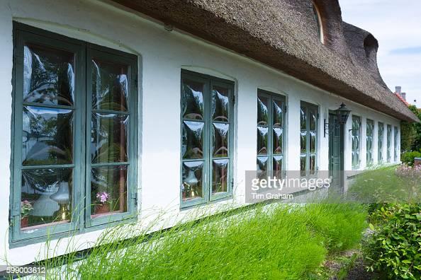 Convex glass windows of thatched cottage at Trofense off Svendborg part of South Funen Archipelago Denmark