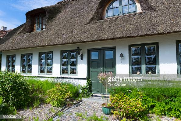 Convex glass windows of thatched cottage at Trofense off Svendborg part of South Funen Archipelago Denmark