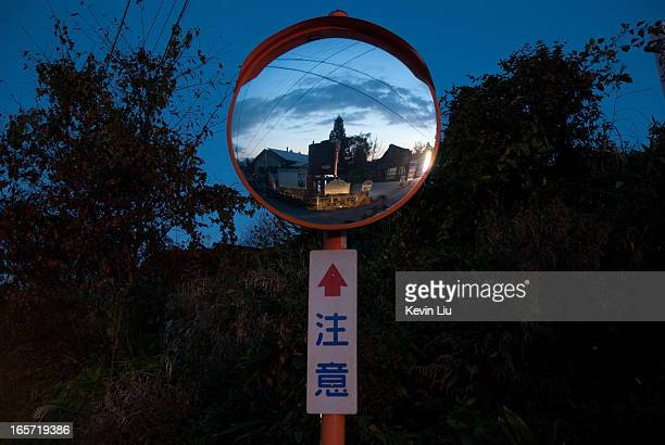 Convex traffic mirror with attention sign at dusk