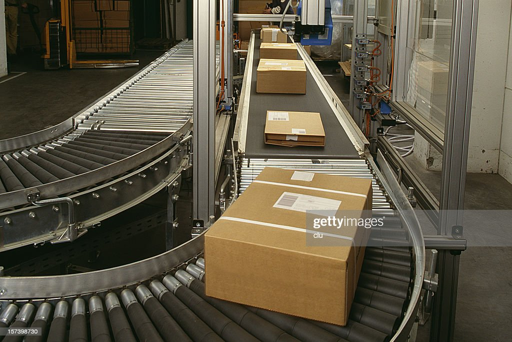 Conveyor belt curve showing brown packed postal boxes