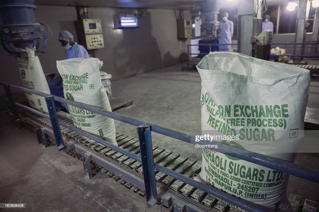 A conveyor belt transports 50-kilogram sacks of sugar in the packaging unit of the Simbhaoli Sugars Ltd. mill in Ghaziabad, Uttar Pradesh, India, on Tuesday, Feb. 26, 2013. India, the world's biggest sugar producer, plans to seek a consensus among various ministries on ending four-decade old state controls on the domestic industry, Food Minister K.V. Thomas said. Photographer: Prashanth Vishwanathan/Bloomberg via Getty Images