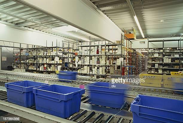 Nastro trasportatore nel magazzino di distribuzione con scatole di plastica blu