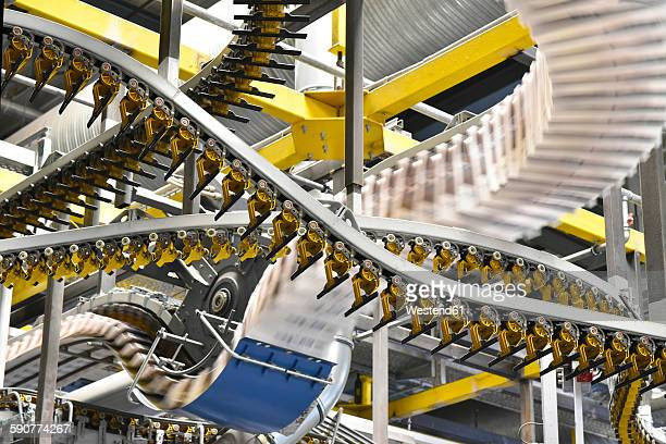 Conveyor belts with newspapers in a printing shop