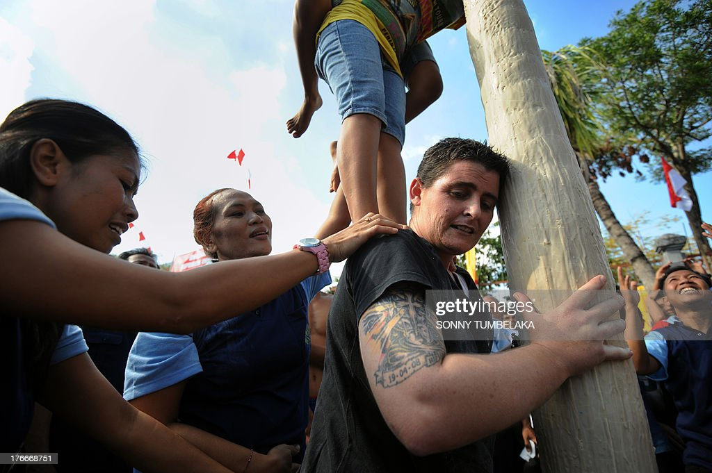 Convicted Australian drug smuggler Renae Lawrence (R-black top) participates with other prisoners as they climb a pole during official ceremonies and games marking Indonesia's 68th Independence Day at Kerobokan prison in Denpasar on Indonesia's resort island of Bali on August 17, 2013. Lawrence -- part of a group of Australian drug traffickers known as the Bali Nine jailed at Kerobokan -- and 11 other foreign prisoners received a recommendation for a six-month cut in her sentence on August 17. Indonesia officials annually offer remissions to some prison sentences on the country's Independence Day for good behaviour. Bali's notorious Kerobokan prison is well known as the place holding several foreign inmates held for high-profile drugs offences.