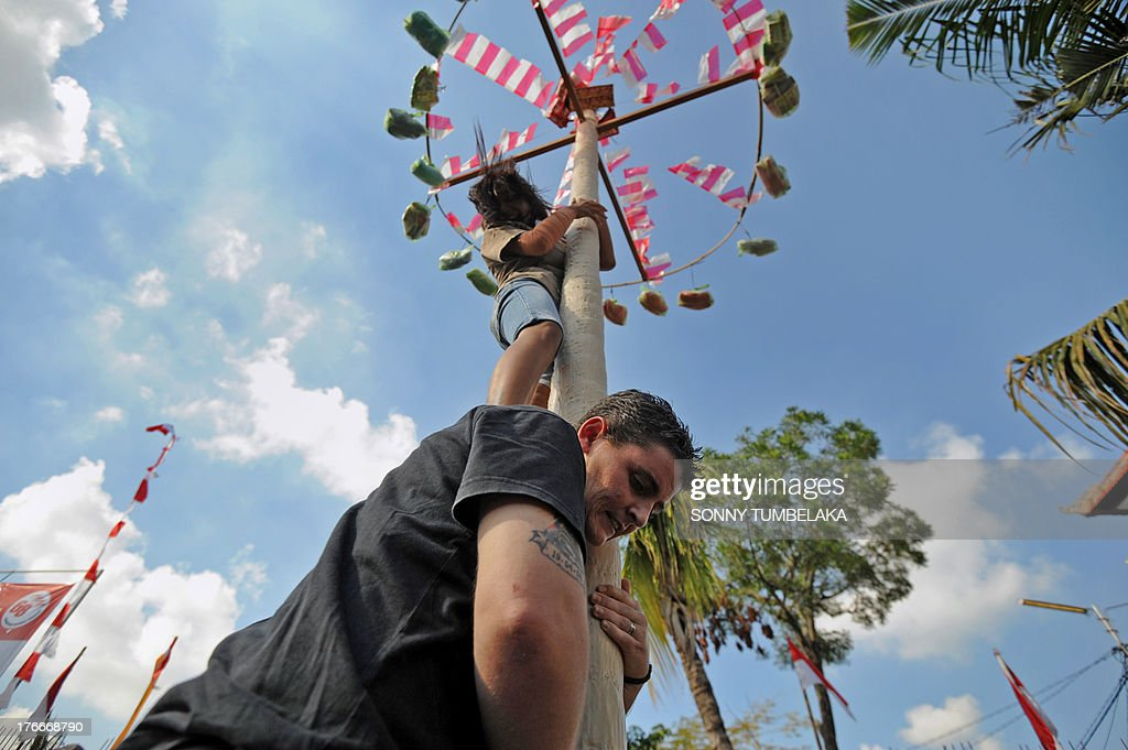 Convicted Australian drug smuggler Renae Lawrence (bottom C-black top) participates with other prisoners as they climb a pole during official ceremonies and games marking Indonesia's 68th Independence Day at Kerobokan prison in Denpasar on Indonesia's resort island of Bali on August 17, 2013. Lawrence -- part of a group of Australian drug traffickers known as the Bali Nine jailed at Kerobokan -- and 11 other foreign prisoners received a recommendation for a six-month cut in her sentence on August 17. Indonesia officials annually offer remissions to some prison sentences on the country's Independence Day for good behaviour. Bali's notorious Kerobokan prison is well known as the place holding several foreign inmates held for high-profile drugs offences. AFP PHOTO / SONNY TUMBELAKA
