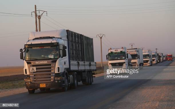 A convoy carrying armoured vehicles and ammunition said to be supplied by the USled coalition is seen driving on a road controlled by the Syrian...