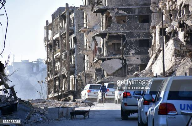 UN convoy drives past damaged buildings in the eastern neighbourhoods of Syria's second city of Aleppo on February 1 2017 / AFP / George OURFALIAN