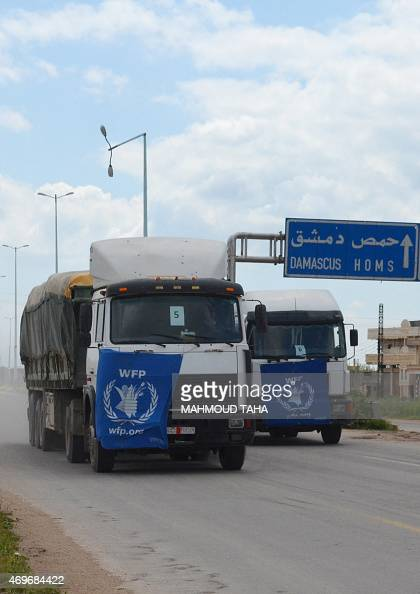 A convoy of 16 trucks carrying international aid from the World Food Programme being escorted by vehicles from the Syrian Arab Red Crescent drive in...