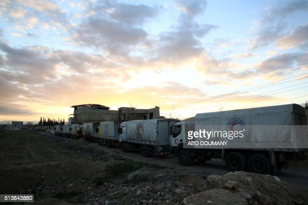 A convoy of aid from the Syrian Arab Red Crescent drives through the rebelheld town of Douma on the outskirts of the capital Damascus on March 4 2016...