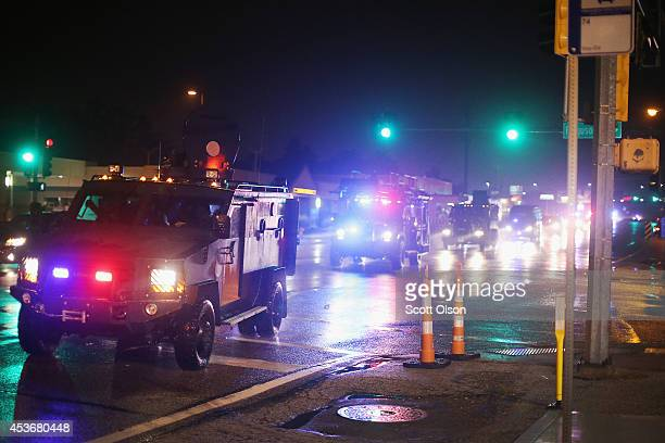 A convoy of armored personnel carriers carrying county police arrive after Missouri State Highway Patrol officers were taunted by demonstrators...