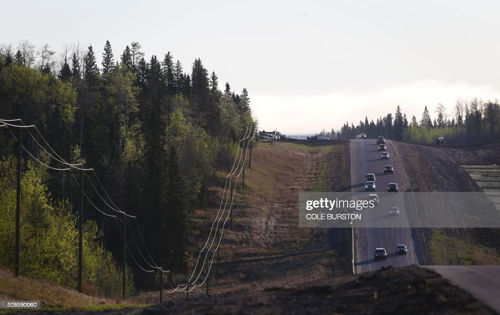 A convoy of cars sporadically heads South down Highway 63 after being stranded at a work camp north of Fort McMurray, Alberta on May 6, 2016. Canada on May 5, 2016 began airlifting to safety up to 25,000 people from the city of Fort McMurray forced from their homes by raging forest fires in Alberta's oil sands region.The authorities ordered the oil city of 100,000 people to be evacuated after firefighters backed by air tankers and helicopters failed to prevent the monster blaze from engulfing entire neighborhoods. / AFP / Cole Burston
