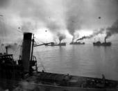 A convoy of coasters sets out at dawn under the protection of escort ships and barrage balloons against air attacks