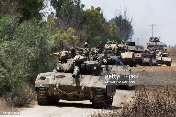 A convoy of Israeli Merkava tanks rolls towards Israels border with the Gaza Strip on July 18 2014 The death toll in Gaza hit 265 today as Israel...