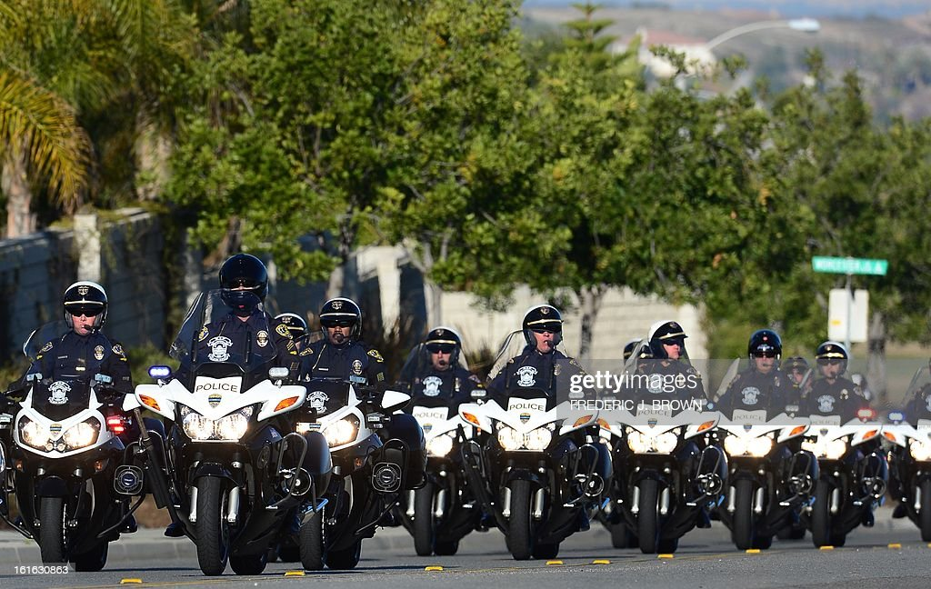 A convoy of motorcycle police ride toward the Grove Community Church for a memorial service for slain Riverside police office Michael Crain in Riverside, California, on February 13, 2013 as motorcycle plice ride past. Law enforcement personnel from across the state, including local dignitaries, military veterans, colleagues, friends and loved ones of the deceased gathered to pay their final respects to the policeman killed last week in what the city's police chief described as a ``cowardly ambush.'' Crain was fatally shot around early last Thursday when he and his partner ran afoul of fugitive Christopher Jordan Dorner, the fired Los Angeles Police Department officer on a killing spree which possibly ended last night in the mountains of nearby Big Bear, authorities allege. AFP PHOTO / Frederic J. BROWN