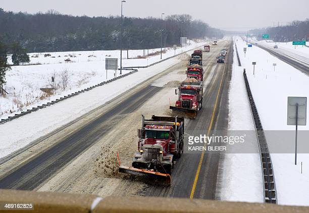 A convoy of plow trucks clear a path on Interstate 66 during a major snowstorm February 13 2014 in Manassas Virginia The biggest storm of the season...