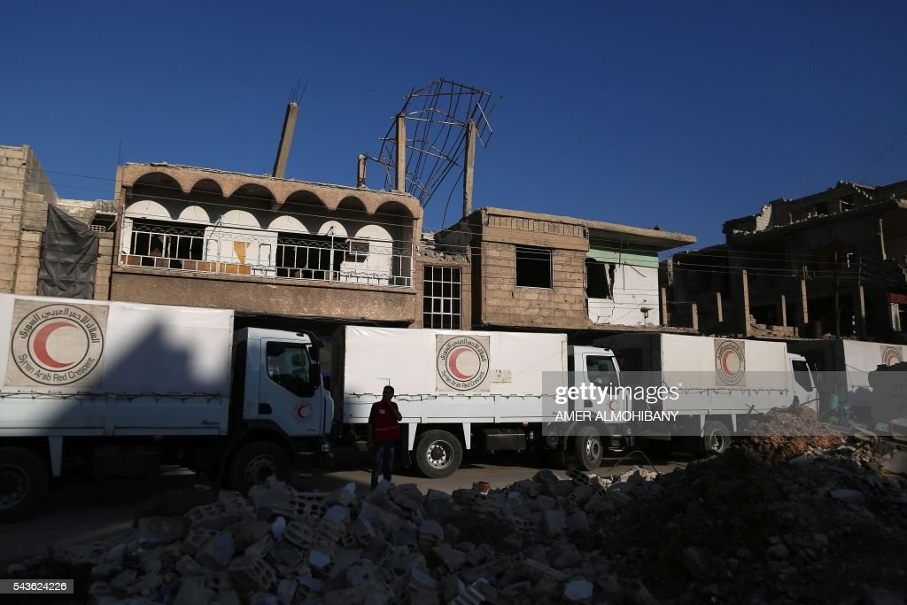 A convoy of Syrian Red Crescent trucks carrying aid drives past destruction in Zamalka , a besieged rebel-held town east of the Syrian capital Damascus, on June 29, 2016. The International Committee of the Red Cross said it was delivering 37 trucks of aid in partnership with the United Nations and Syrian Arab Red Crescent. The convoy includes food parcels, wheat flower, and hygiene kits for the 20,000 people living in the towns of Zamalka and Erbin. ALMOHIBANY