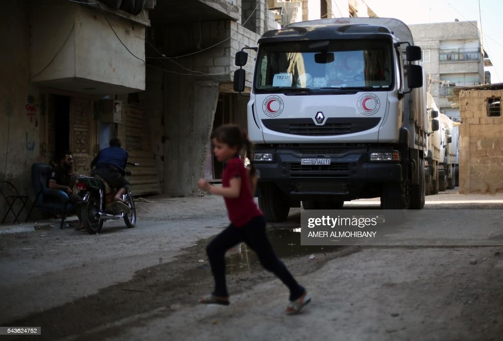 A convoy of Syrian Red Crescent trucks carrying aid drives through Zamalka, a besieged rebel-held town east of the Syrian capital Damascus, on June 29, 2016. The convoy entered the besieged Syrian towns of Zamalka and Erbin near Damascus, the first aid delivered to them since 2012, the International Committee of the Red Cross told AFP. ICRC added it was delivering 37 trucks of aid in partnership with the United Nations and Syrian Arab Red Crescent. The convoy includes food parcels, wheat flower, and hygiene kits for the 20,000 people living in the besiged towns. ALMOHIBANY