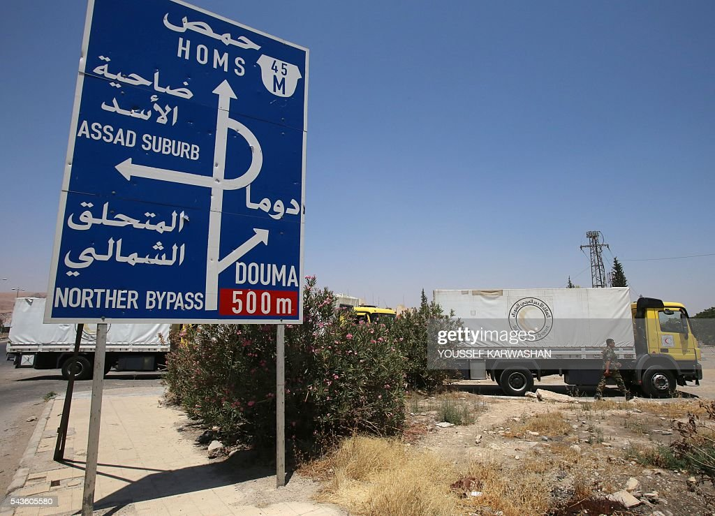 A convoy of Syrian Red Crescent trucks drives past a road sign at the entrance of Harasta, a besieged suburb of the capital Damascus, on June 29, 2016, on its way to the rebel-held towns of Zamalka and Erbin. The convoy of food and medicine entered Zamalka and Erbin, the first aid delivered to them since 2012, the International Committee of the Red Cross told AFP. / AFP / YOUSSEF