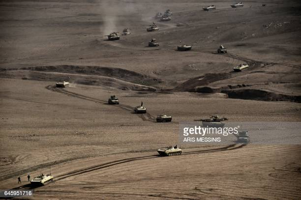 A convoy of tanks and armoured vehicles of the Iraqi army's 34th brigade advances near Talul alAtshana on the southwestern outskirts of Mosul on...