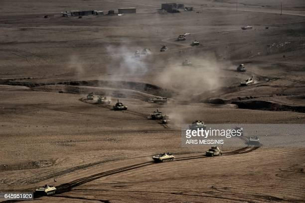 TOPSHOT A convoy of tanks and armoured vehicles of the Iraqi army's 34th brigade advances near Talul alAtshana on the southwestern outskirts of Mosul...