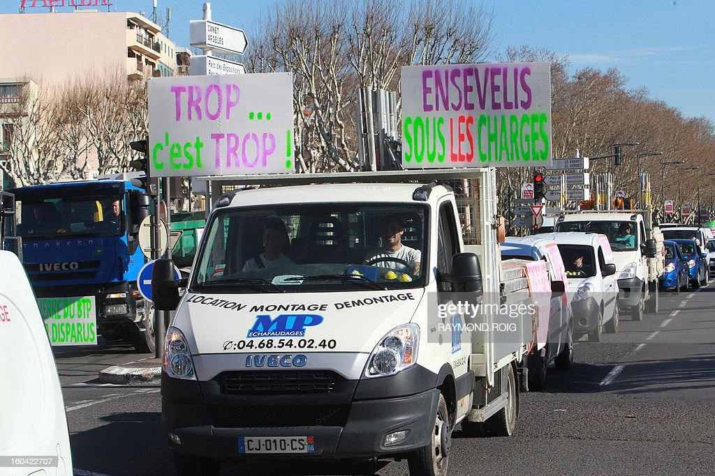 A convoy of truck with a sign reading 'Too much is too much...buried under taxes ' drives by in Perpignan as construction workers protested against high employer taxes on January 31, 2013. AFP PHOTO / RAYMOND