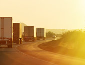 Semi trucks driving through the desert at sunrise.