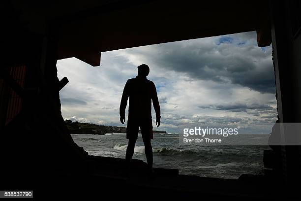 Coogee SLSC volunteer Benjamin Heenan poses against the gaping hole left in the Coogee SLSC on June 7 2016 in Sydney Australia A huge wave hit the...