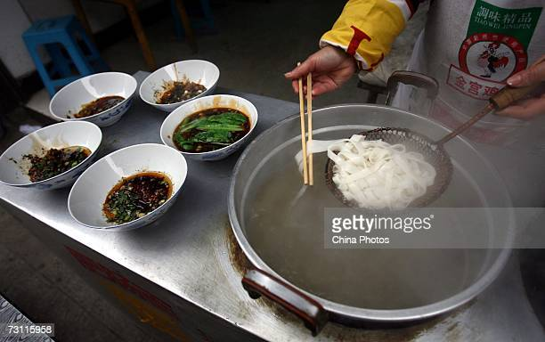 A cook boils rice noodles at a noodle workshop in Wansheng District on January 25 2007 in Chongqing Municipality China Rice noodles are made from...