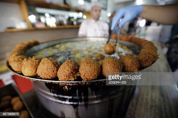 A cook fries Falafel balls at a restaurant in Jounieh north of the Lebanese capital Beirut on October 17 2014 Falafel is a deepfried ball or patty...