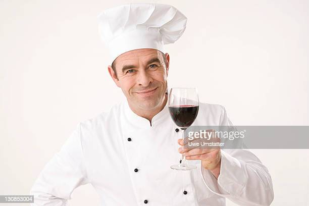 Cook holding a glass of red wine