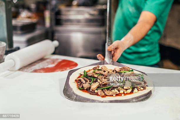 cook holding pizza on peel