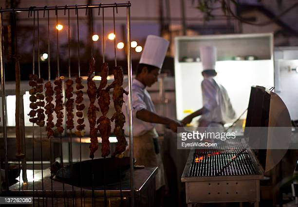 A cook in a restaurant prepare a traditional Tandoori barbeque with chicken at December 24 2011 in Kozhikode Kerala India