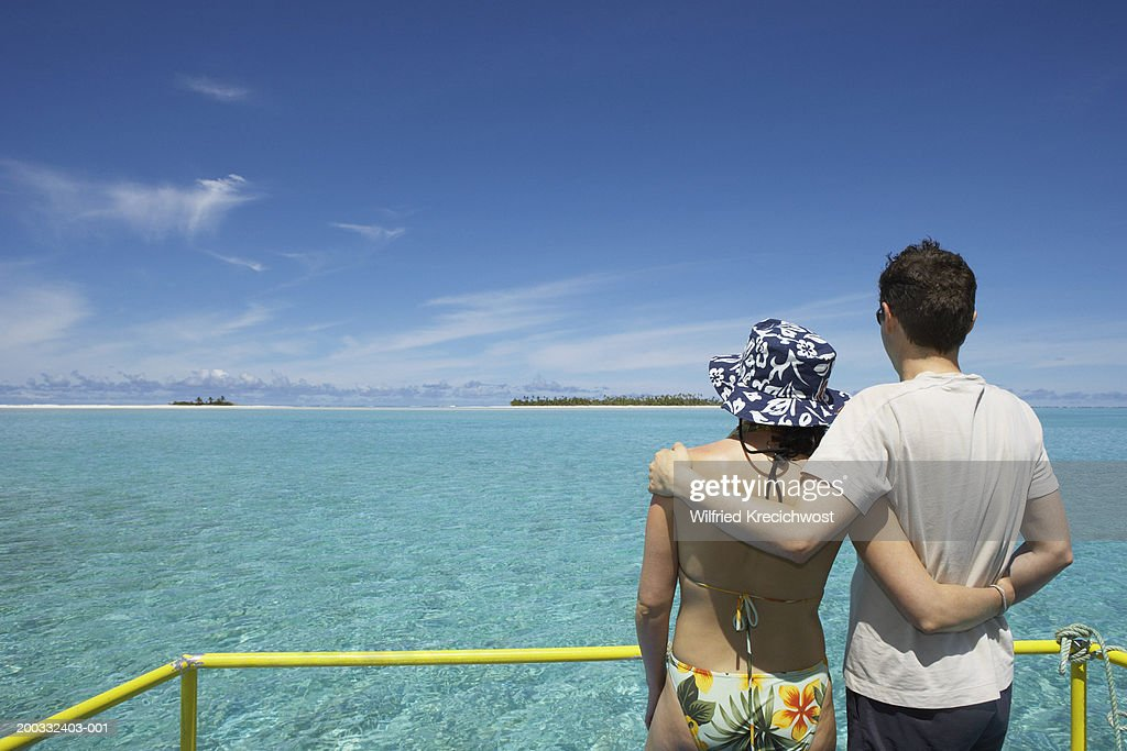 Cook Islands, Aitutaki, couple arm in arm on boat, rear view : Stock Photo