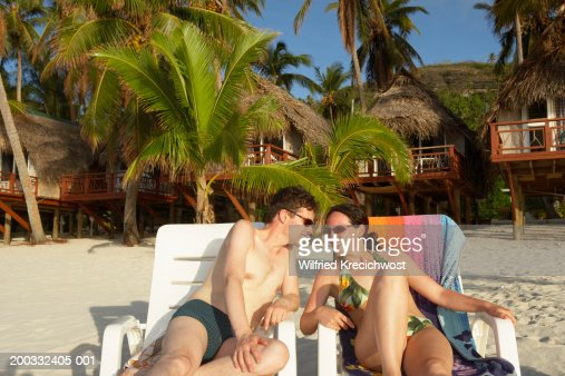 Cook Islands, Aitutaki, couple sunbathing, smiling at each other : Stock Photo