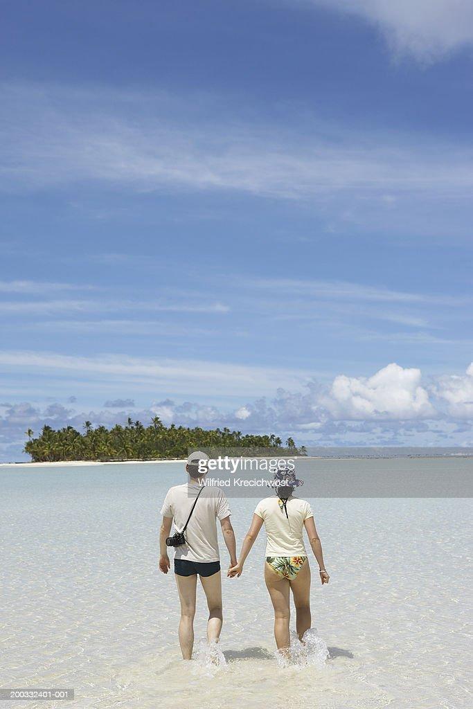 Cook Islands, Aitutaki, couple walking in lagoon, rear view : Stock Photo