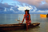 Cook Islands, young woman sitting on edge of canoe