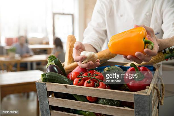 Cook of a bistro with wooden box of vegetables
