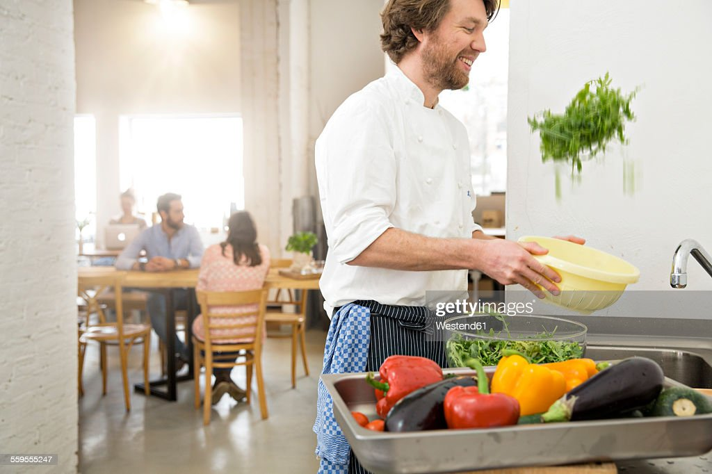 Cook of a little restaurant preparing lettuce in the kitchen : Stock Photo