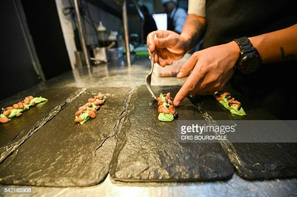 A cook places final touches on a dish created by Peruvian Nikkei chef Mitsuharu Tsumura known as Misho at the Maido highcuisine restaurant in Lima on...