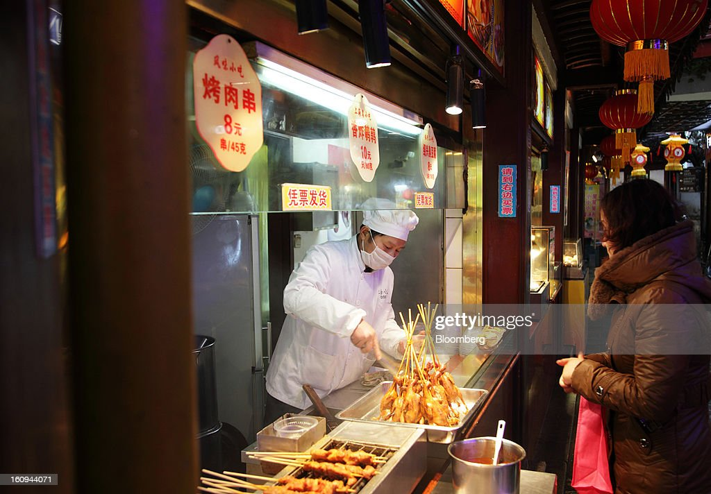 A cook prepares fried chicken as a customer looks on at a market in Shanghai, China, on Thursday, Feb. 7, 2013. China's consumer prices rose 2 percent in January from a year earlier while the producer-price index dropped 1.6 percent, the National Bureau of Statistics said today in Beijing. Photographer: Tomohiro Ohsumi/Bloomberg via Getty Images