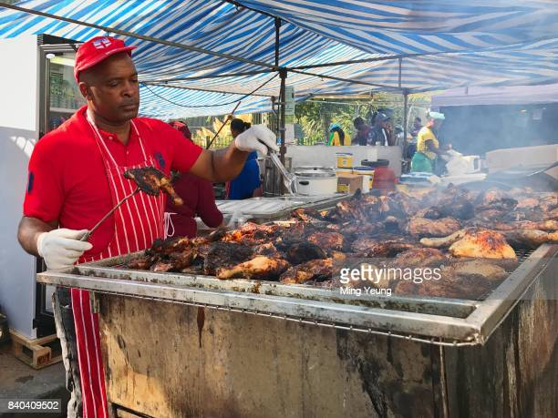 A cook prepares the carnival favourite jerk chicken on the BBQ at Notting Hill Carnival on August 27 2017 in London England